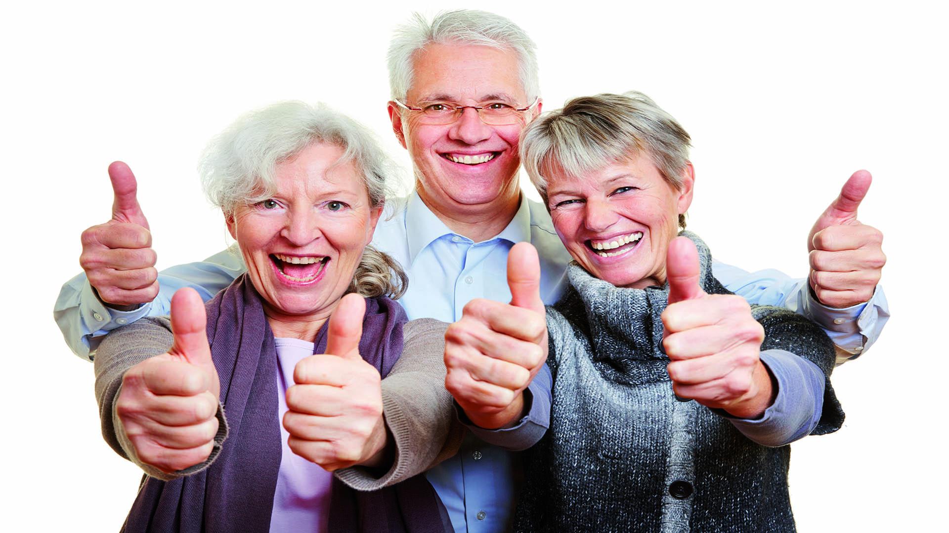 Drei Senioren halten glücklich Daumen hoch
